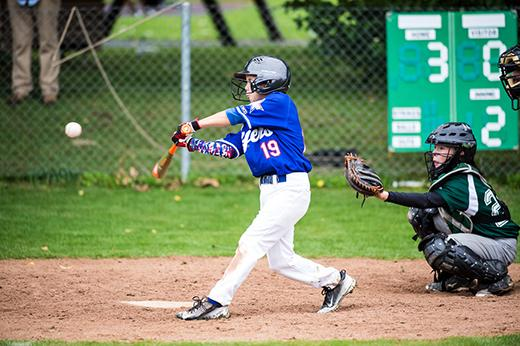 Juvenile baseball batter hitting the ball